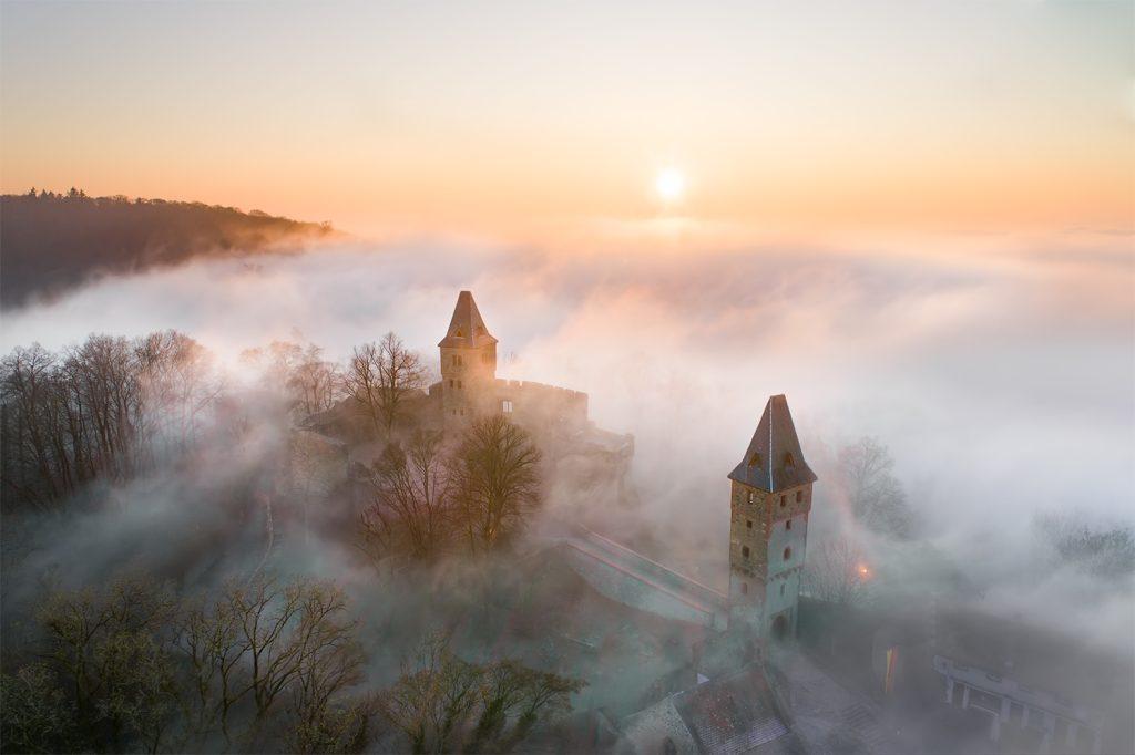 Burg Frankenstein über dem Nebel, fotografiert mit einer Drohne.