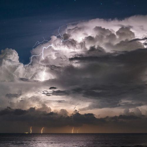 Eine erleuchtete Cumulonimbuswolke bei Nacht über dem Meer.