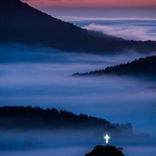 Ein Gipfelkreuz im Pfälzerwald bei Nebel.
