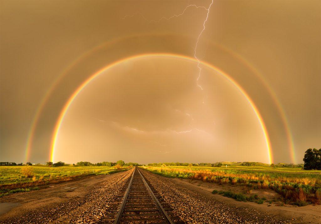 Regenbogen mit Blitzen bei einem Gewitter.