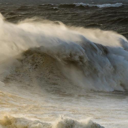 Eine sich brechende Welle am Surfstrand von Nazaré.