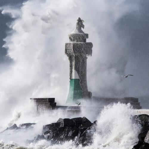 Wellen brechen über dem vereisten Leuchtturm von Sassnitz bei Sturm.