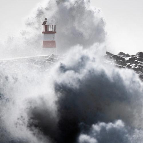 Wellen brechen sich über einem Leuchtturm in Portugal.
